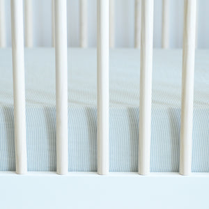 cotton muslin crib sheet with very small grey stripes in a crib