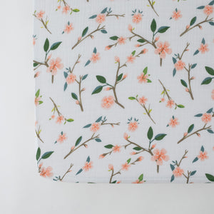 cotton muslin crib sheet with pink peach blossoms blooming on a branch with leaves