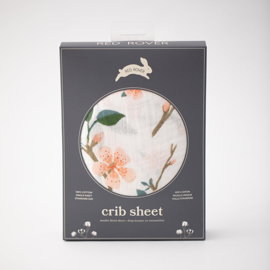 cotton muslin crib sheet with pink peach blossoms blooming on a branch with leaves in Red Rover packaging