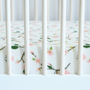 cotton muslin crib sheet with pink peach blossoms blooming on a branch with leaves in a crib