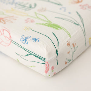 cotton muslin changing pad cover with blue, pink, yellow, and red flowers on a white background