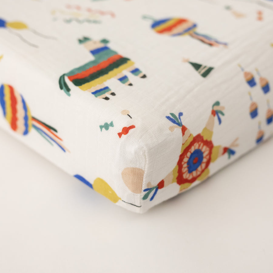 cotton muslin changing pad cover with party them print including pinatas, confetti, cake, balloons, party hats and more