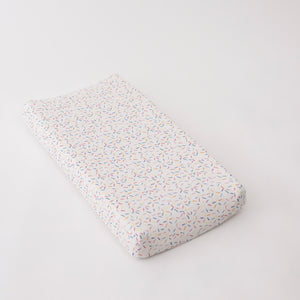 cotton muslin changing pad cover with blue, pink, yellow, red, and green sprinkles on a white background