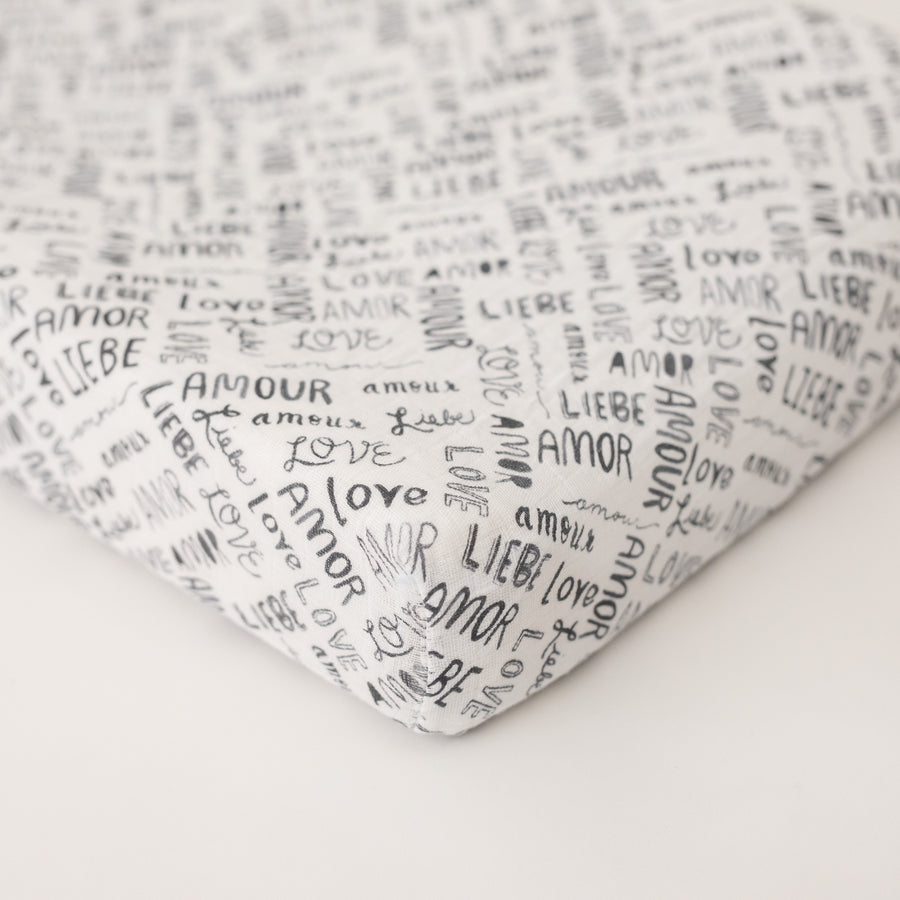 "cotton muslin changing pad cover with the word ""love"" in multiple different languages in grey writing on a white background"