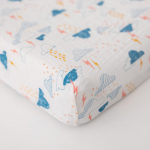 cotton muslin changing pad cover with blue clouds and yellow and pink lightening on a white background