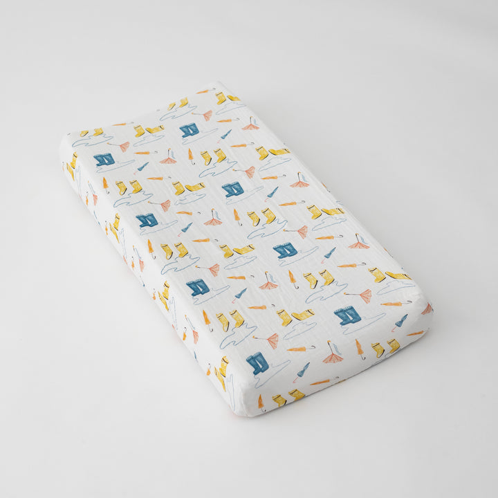 cotton muslin changing pad cover with yellow and blue rain boots, puddles, and orange umbrellas