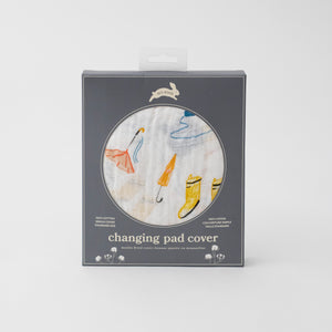 cotton muslin changing pad cover with yellow and blue rain boots, puddles, and orange umbrellas in Red Rover packaging