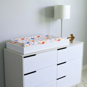cotton muslin changing pad cover, with colorful whole and sliced apples on a changing table
