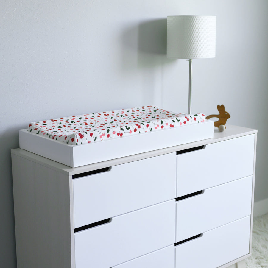 cotton muslin changing pad cover, with red and pink cherries and green leafs on a changing table