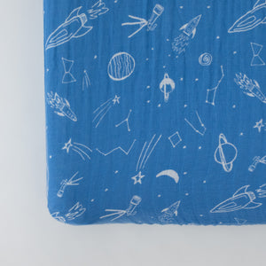 cotton muslin changing pad cover with white stars, planets, telescopes, and rocket ships all on a blue background