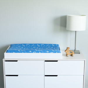 cotton muslin changing pad cover with white stars, planets, telescopes, and rocket ships all on a blue background on a changing table