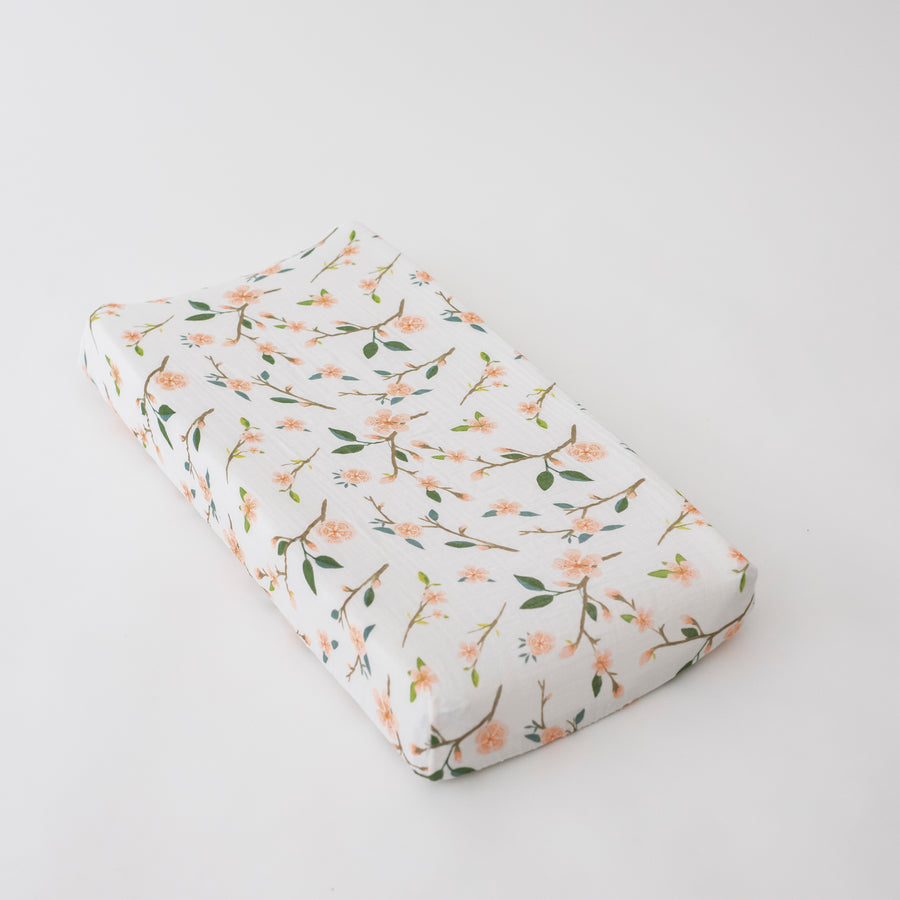 cotton muslin changing pad cover with pink peach blossoms blooming on a branch with leaves