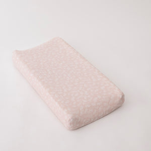 cotton muslin changing pad cover with small white flowers on a blush background