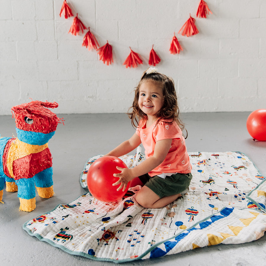 toddler sitting on a party time quilt playing with a balloon and a pinata