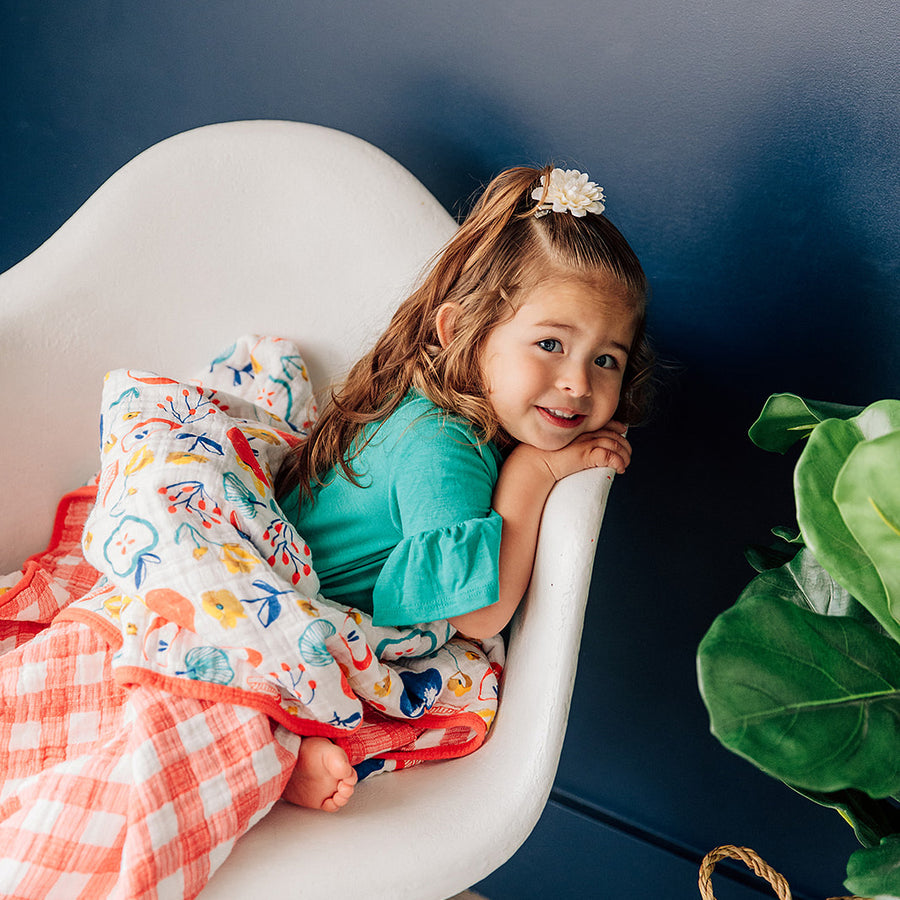 toddler sitting on a chair cuddling an apple slice quilt