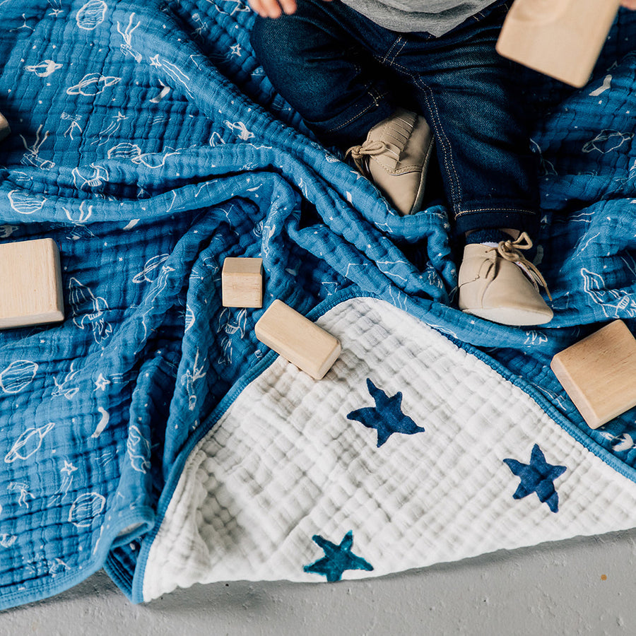 baby sitting on a sun moon stars quilt playing with blocks