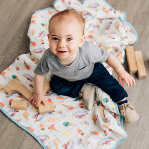 smiling baby sitting on a ice cream parlor quilt playing with blocks