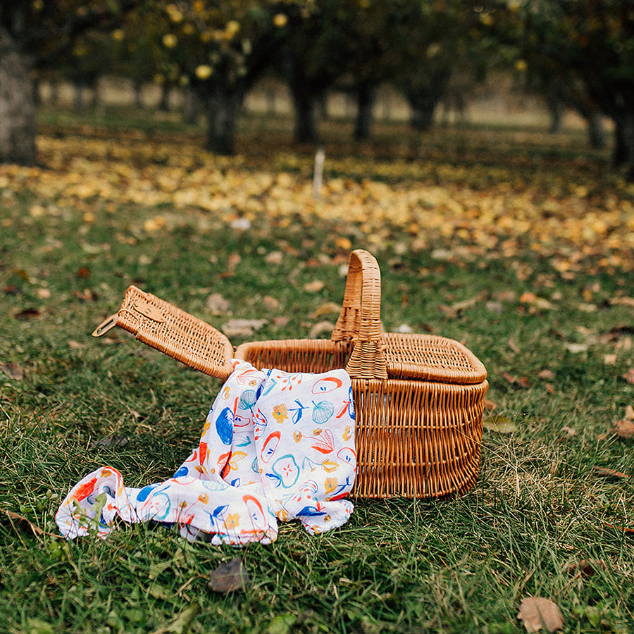 apple slice swaddle blanket in a picnic basket