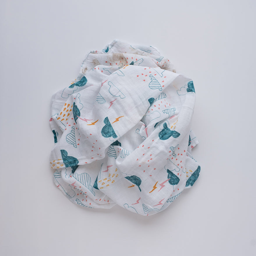 single swaddle blanket with blue clouds, yellow and pink lightening and rain