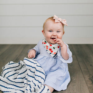smiling baby wearing cherries reversible bandana bib with navy stripe blanket