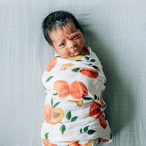 baby swaddled in a peaches blanket laying on a micro grey crib sheet