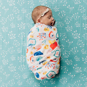 sleeping baby swaddled in an apple slice blanket laying on a teal buds crib sheet