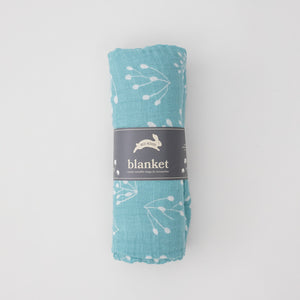 single swaddle blanket with small flower buds on a teal background rolled in Red Rover packaging
