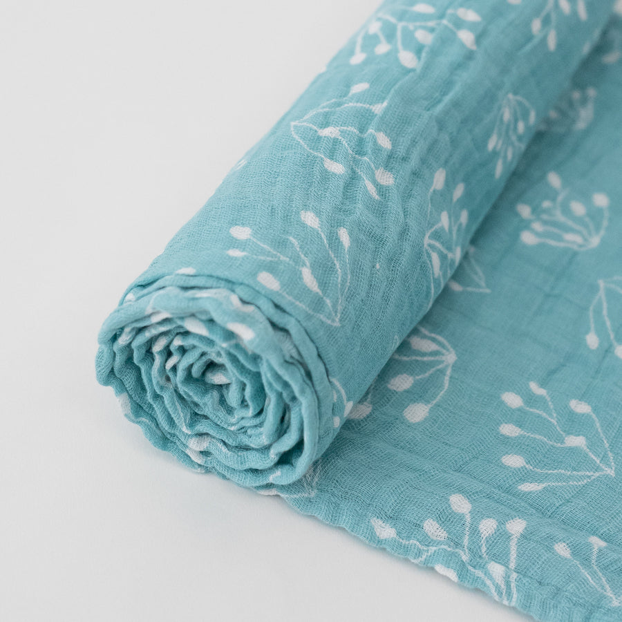 single swaddle blanket with small flower buds on a teal background