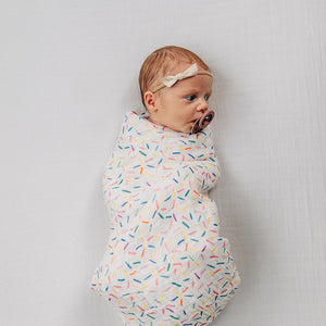 baby swaddled in a sprinkles blanket laying on a white crib sheet