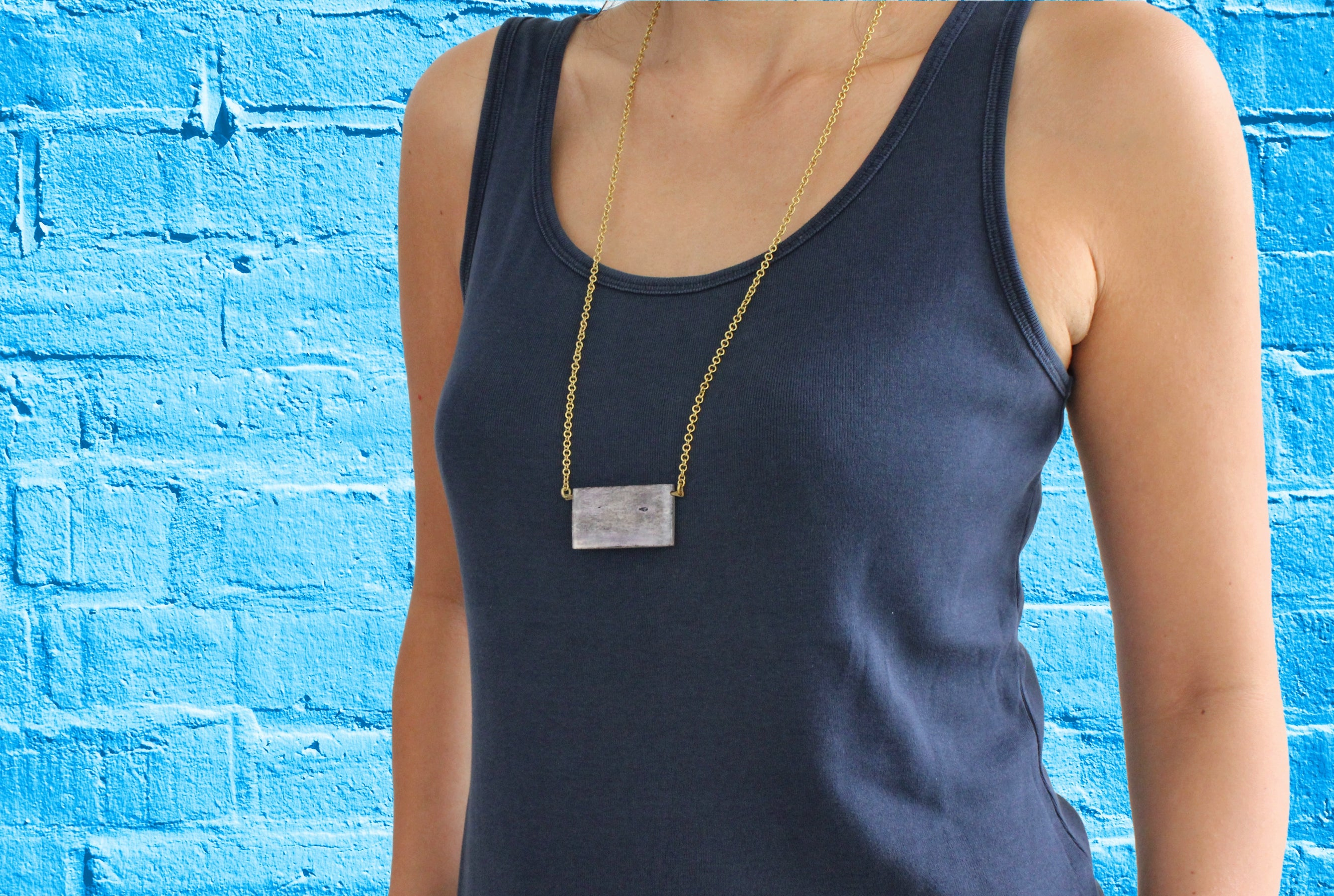 African brass necklace grey bone body blue background