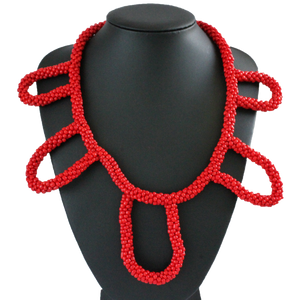 African handmade necklace with red beads on black display
