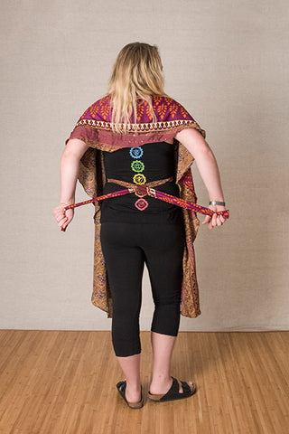 Step 3: Pull the ties behind your back again and cross them, switching hands and bringing them back to the front in the opposite hands.