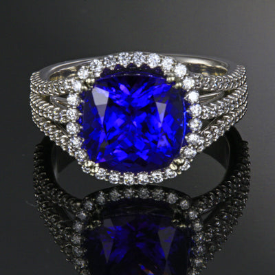 Ladies' 18k white gold tanzanite ring designed by Steve Moriarty, with one blue violet exceptional color, VS+ clarity square cushion tanzanite. The tanzanite weighs 4.25 carats, has been color enhanced by heating, measures 9.7 mm wide by 9.7 mm long by 6.