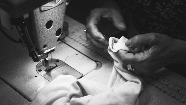 Hands of a women snipping threads at her sewing machine making Asmuss clothing