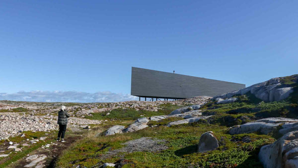 Side view of the Long Studio on Fogo Island with the mother of the Asmuss founders walking towards it