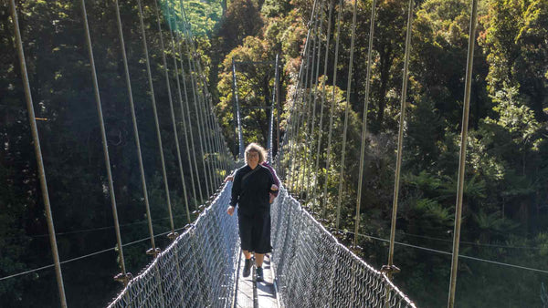 Crossing a swing bridge on the Hollyford Track wearing Asmuss