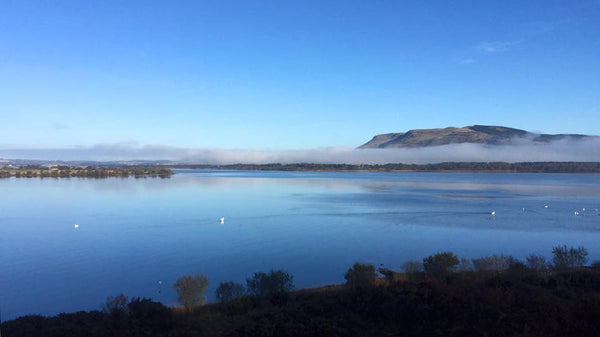 Loch Leven, Scotland, with clear blue sky and a line of mist in front of Bishops Hill