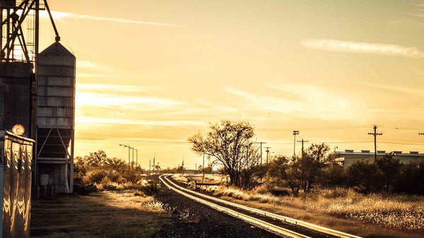 Sunset on rail tracks beside factory silos in Marfa, Texas