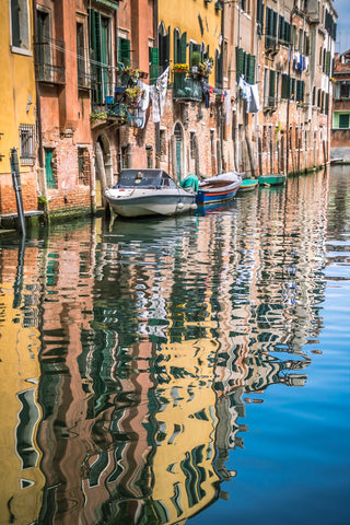 The buildings and boats of Venice reflected in the canal