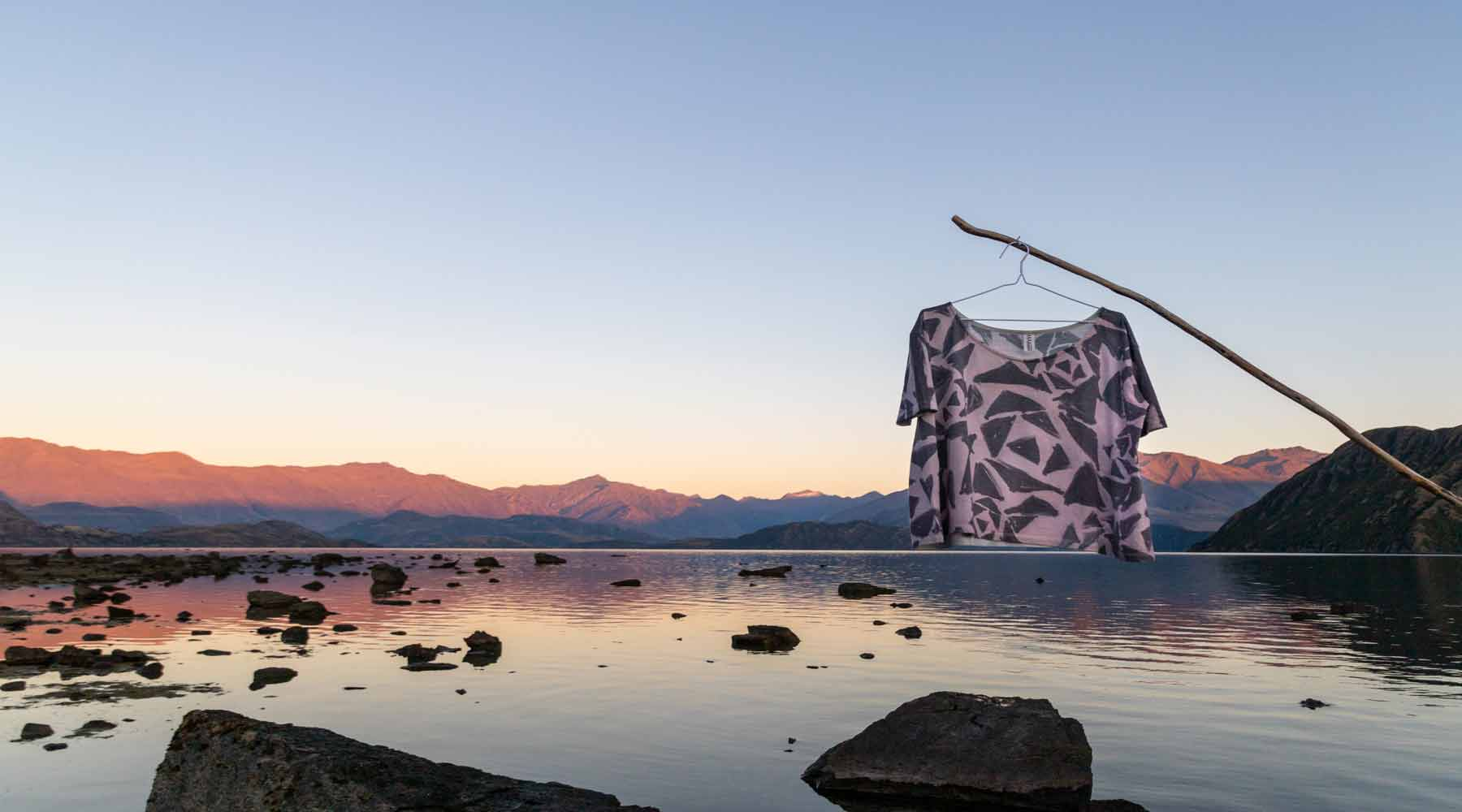 Asmuss Black Rose Tshirt on a coat hanger hung off a stick above the still water and rocks of Lake Wanaka while the sun rises on the mountains in the distance