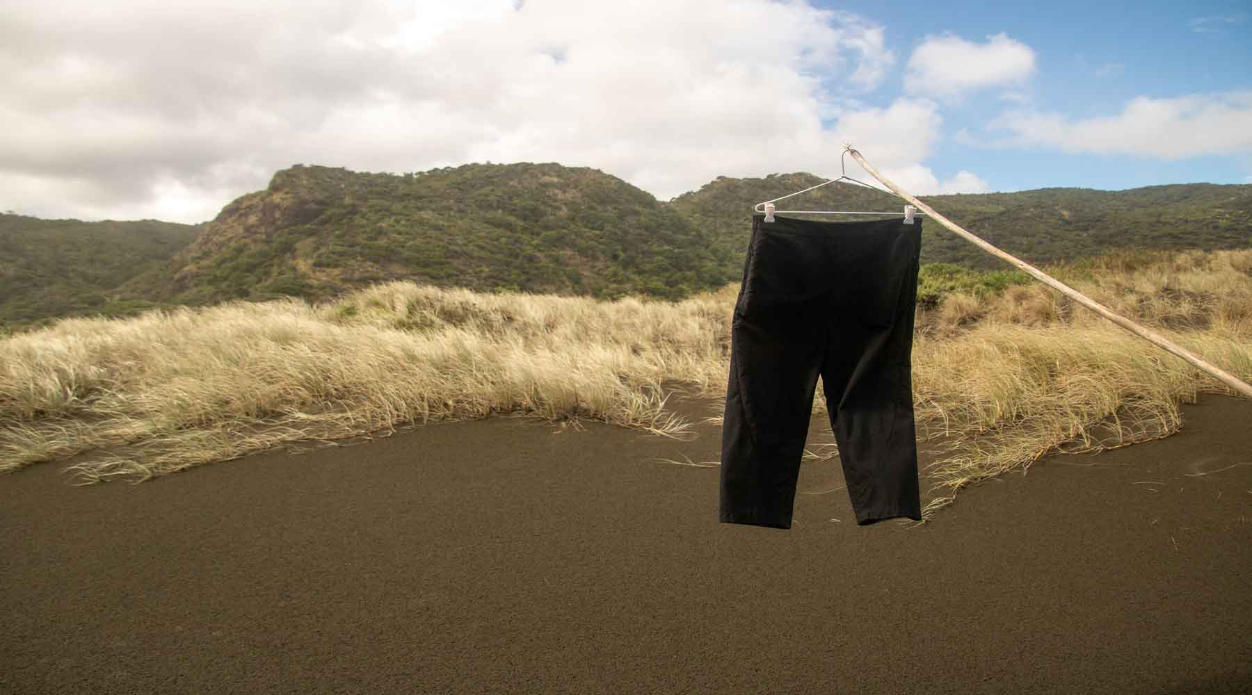 Asmuss Panelled Trousers hanging in front of the black sand dune of Karekare New Zealand