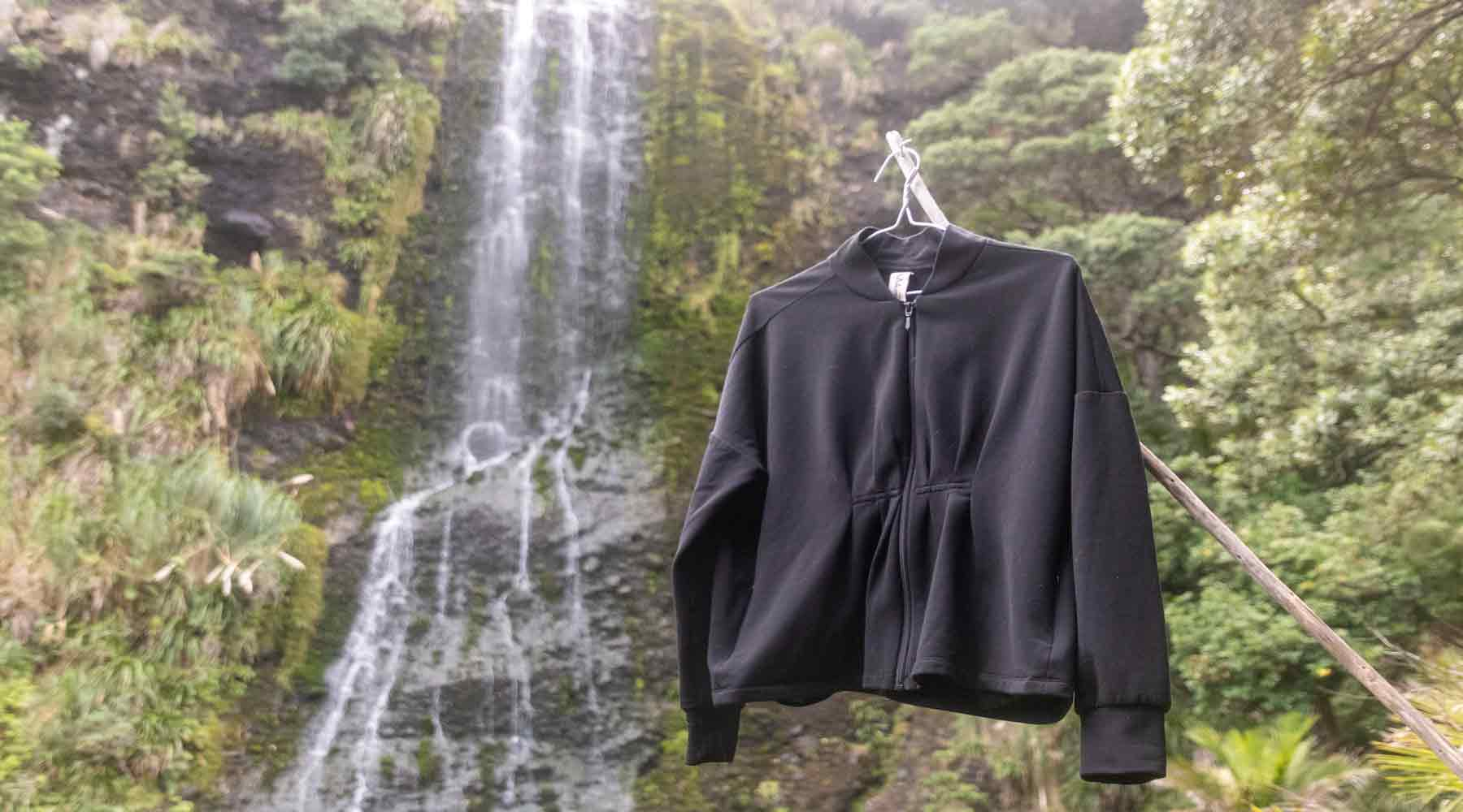 Asmuss Pleated Zip Through Sweater in front of the Karekare Falls New Zealand