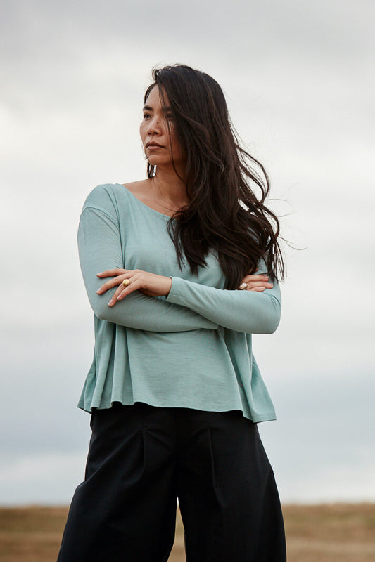 A strong modern woman wearing the Asmuss A-line Long Sleeve T-shirt in Sea Green taking on the world