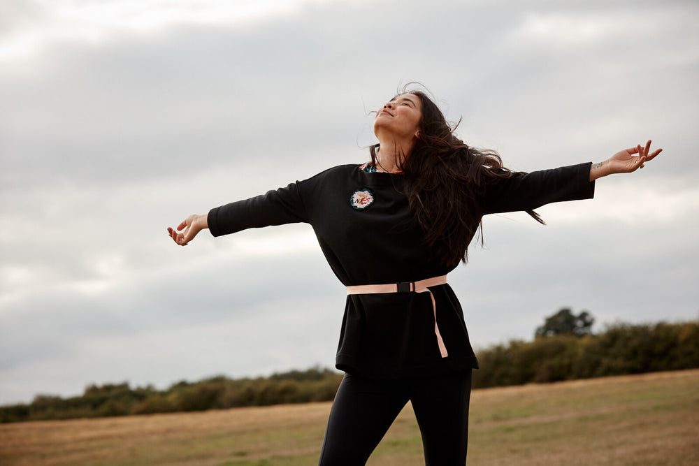 Asmuss Oversized Boatneck Sweatshirt being worn by a modern woman with arms wide open to new adventures and experiences