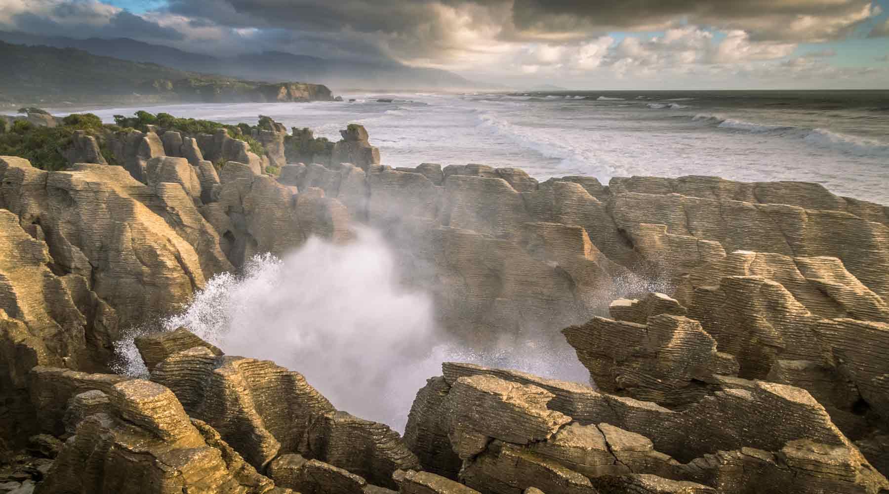 Water coming up through a blow hole in the Punakaiki pancake rocks as the sun goes down to the right