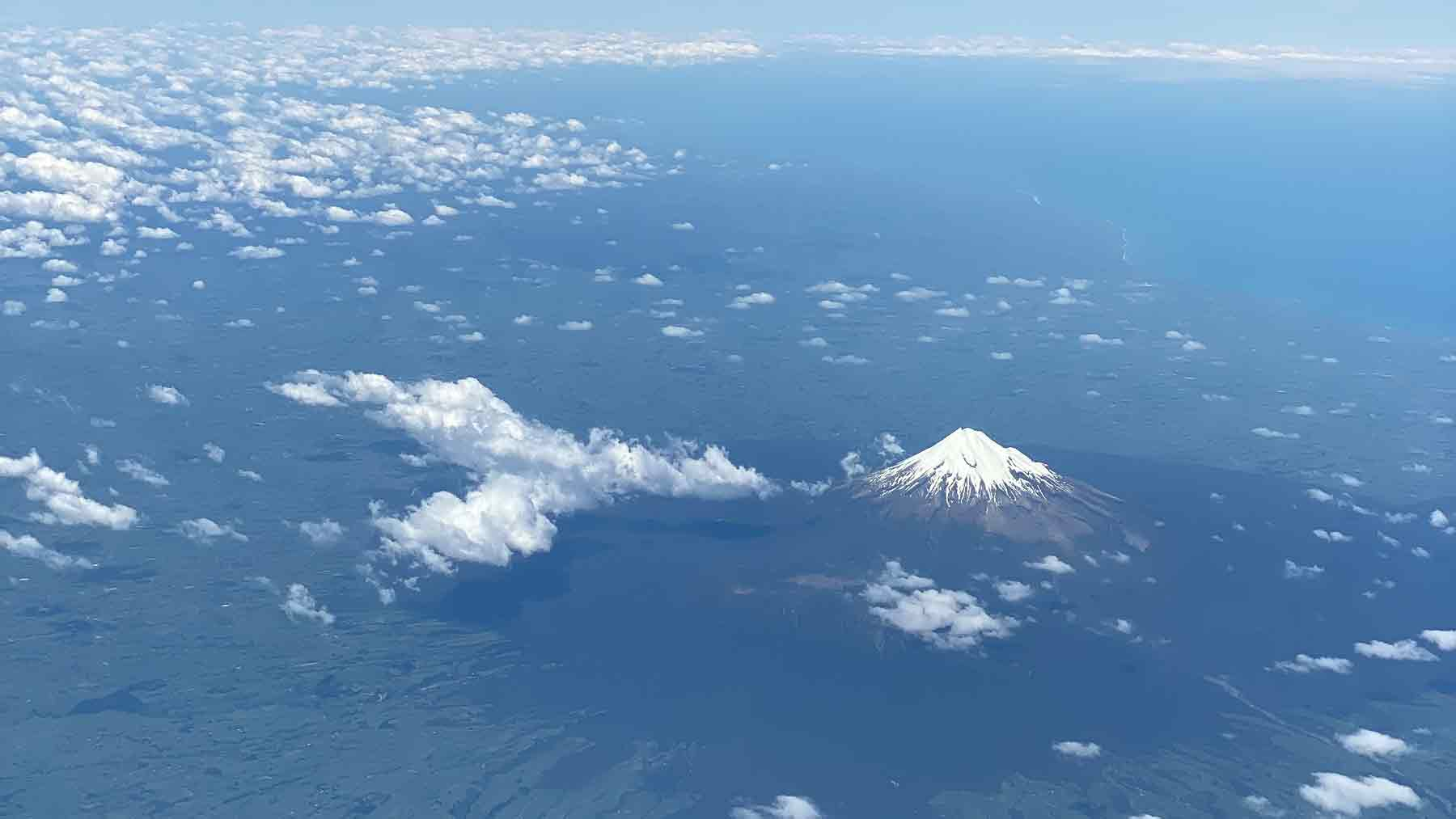 Snow covered Mount Taranaki and the coast of Taranaki from an airplane with little fluffy white clouds
