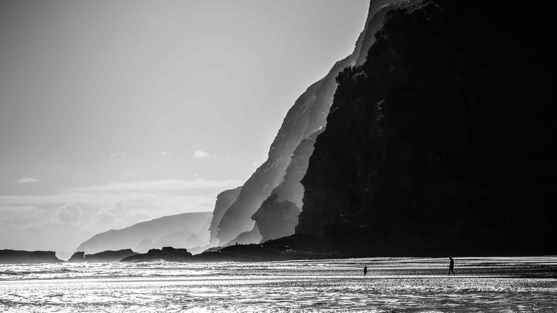 Clothing Care. Try not to over wash your clothes. Black and white image of Karakare beach and cliffs in Auckland New Zealand