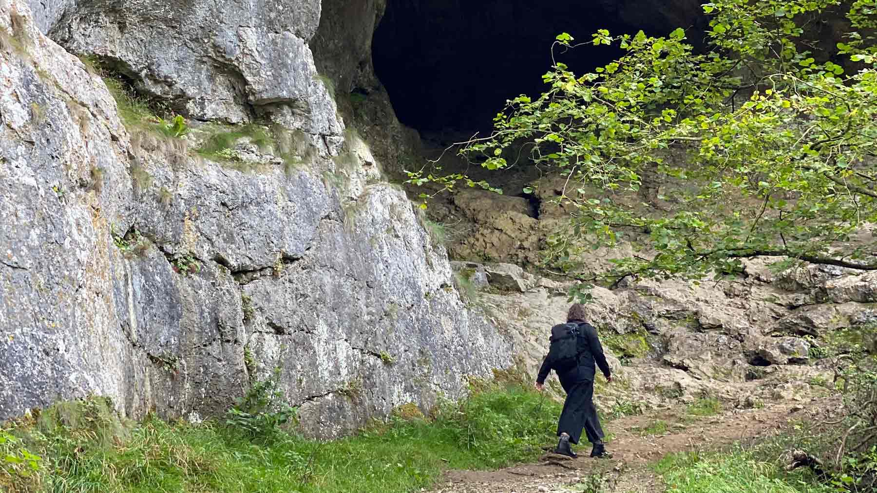 Clare walking near a cave next to the River Dove in the Peak District wearing the Asmuss Wide Leg Trousers and Pleated Zip Through Sweat