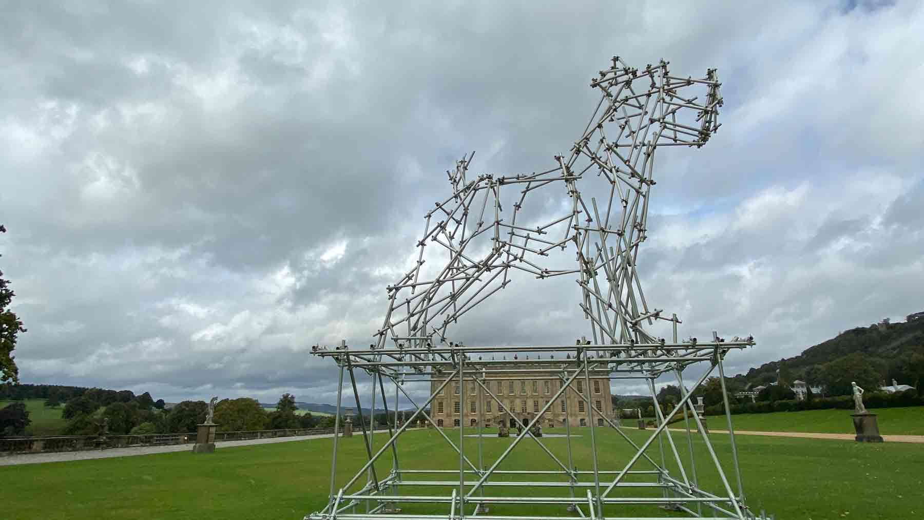 Chatsworth seen through a large dog sculpture made from scaffolding