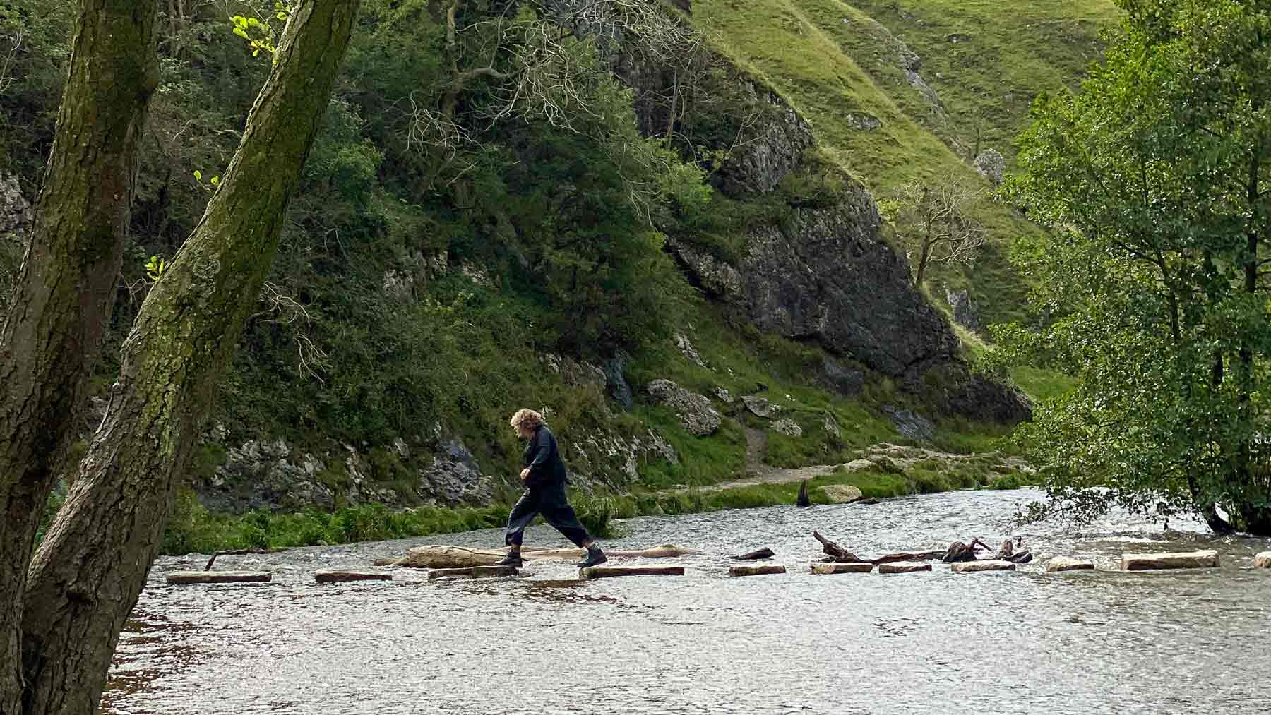 Clare crossing the Dovedale Steeping Stones, wearing Asmuss, in the Peak District